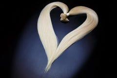 Het materiaal van de haaruitbreiding van natuurlijk blondehaar hartvorm op een donkere achtergrond stock foto