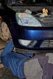 Het mechanisch werk die ter plaatse herstellend een oude auto liggen stock foto's