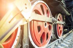 Het mechanisme van de treinaandrijving en rode wielen van een oude sovjetstoomlocomotief Heldere stralen van de het plaatsen zon stock afbeelding