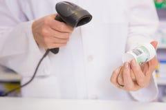 Het medicijn van het apothekeraftasten met een scanner Stock Foto's
