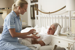Het Medicijn van verpleegstersgiving senior male in Bed thuis Stock Foto's
