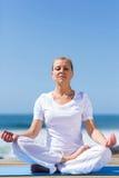 Het medio leeftijdsvrouw mediteren Stock Afbeelding