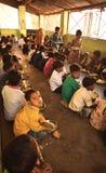 Het medio programma van de dagmaaltijd, in een Indisch overheidsinitiatief, is lopend in een lage school De leerlingen nemen hun  royalty-vrije stock afbeelding