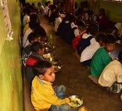 Het medio programma van de dagmaaltijd, een Indisch overheidsinitiatief, is lopend in een lage school De leerlingen nemen hun maa stock afbeeldingen