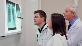 Het medische team analizes röntgenstraal op x-ray meningsdoos stock foto