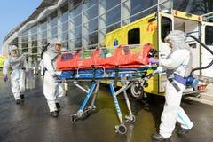 Het medische team duwende brancard van HAZMAT stock afbeeldingen