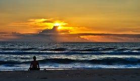 Het mediteren op het strand bij zonsopgang stock foto's