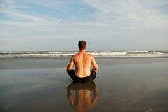 Het mediteren van de mens op strand Stock Foto's