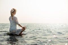 Het mediteren van de vrouw bij het overzees royalty-vrije stock fotografie