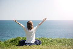 Het mediteren van de vrouw bij het overzees stock afbeeldingen