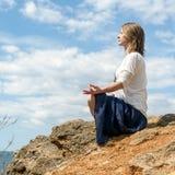 Het mediteren van de vrouw bij het overzees stock foto