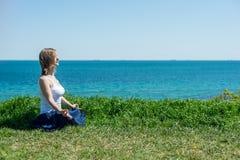 Het mediteren van de vrouw bij het overzees stock fotografie