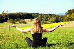 Het mediteren van de vrouw op het gebied Stock Foto's