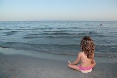 Het mediteren van het meisje op het strand stock fotografie