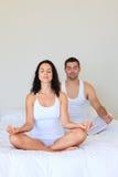 Het mediteren van het paar in bed Royalty-vrije Stock Afbeeldingen