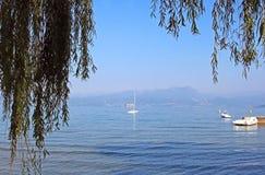 Het meer Garda met sommige boten, die door takken van het huilen worden ontworpen zal Royalty-vrije Stock Afbeeldingen