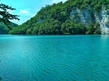 Het meer met lichtgevend azuurblauw-gekleurd water Groen en rotsen De Meren van Plitvice, Kroatië royalty-vrije stock foto