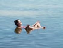 Het meer met zout water Baskunchak Mooie vrouw sunbathin Royalty-vrije Stock Afbeelding