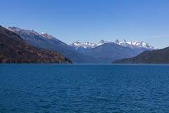 Het meer Puelo met ver sneeuw-caped bergen stock afbeeldingen