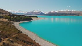 Het meer Pukaki, zet Cook met blauwe hemel met en sneeuw op behandelde Zuidelijke Alpen, Nieuw Zeeland stock footage