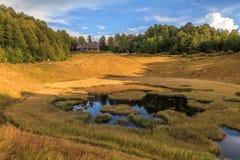 Het meer van de Khmelevskoyeberg in karst holte die met van de berg het bosang van de de herfstkaukasus rode gele gras bij zonson royalty-vrije stock foto