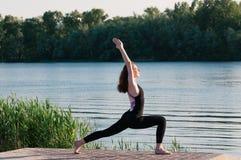 Het meer van de de yogazonsopgang van de meisjesschoonheid in openlucht royalty-vrije stock fotografie