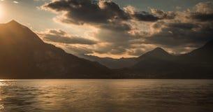 Het meer van de zonneschijnberg bij zonsondergang bewolkte hemel royalty-vrije illustratie