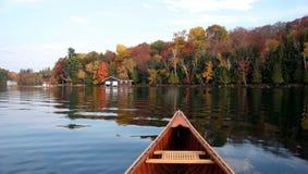 Het meerbezinning van de herfst met een kano Stock Afbeelding