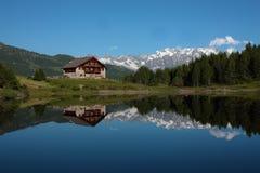 Het meerlandschap van het huis en van de berg Stock Foto's
