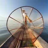 Het meervisser van Birma Myanmar Inle op boot die vissen vangen stock foto's
