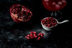 Het meeste seducive fruit - Verleidende granaatappel, rode zaden en vers sap met de toevoeging van ijs op een zwarte, steenachter stock fotografie