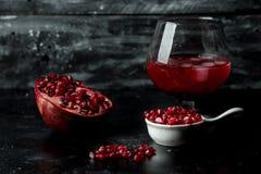 Het meeste seducive fruit - Verleidende granaatappel, rode zaden en vers sap met de toevoeging van ijs op een zwarte, steenachter royalty-vrije stock afbeeldingen