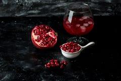 Het meeste seducive fruit - Verleidende granaatappel, rode zaden en vers sap met de toevoeging van ijs op een zwarte, steenachter royalty-vrije stock afbeelding