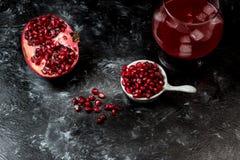 Het meeste seducive fruit - Verleidende granaatappel, rode zaden en vers sap met de toevoeging van ijs op een zwarte, steenachter royalty-vrije stock fotografie