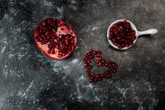 Het meeste seducive fruit voor Valentijnskaartendag - de Verleidende granaatappel, rode zaden schikte in de vorm van een hart royalty-vrije stock foto