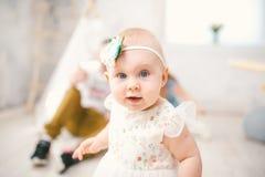 Het meisje één jaar met blauw ogenblonde in een weelderige witte kleding is tevreden en speelt in een heldere ruimte op achtergro stock afbeeldingen