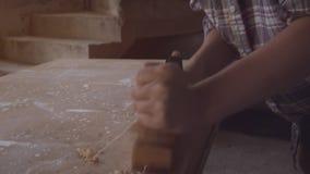 Het meisje aan het werk in een timmerwerkworkshop, met handplaner Close-up stock footage