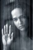 Het meisje achter glas stock foto
