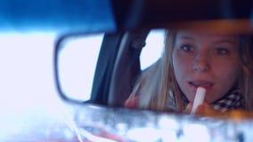 Het meisje achter het wiel van een autolippenstift in de achteruitkijkspiegel 4K 30fps ProRes stock footage