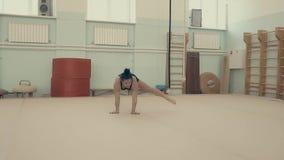 Het meisje is atletisch, in de gymnastiek, uitvoert een acrobatische reeks, langzame motie stock videobeelden