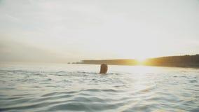 Het meisje baadt in avond in rivier voor het plaatsen van zon en bespat water stock footage