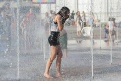 Het meisje baadt in de fontein in hete dag Royalty-vrije Stock Fotografie