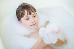 Het meisje baadt in een badkamers en glimlacht Royalty-vrije Stock Afbeelding