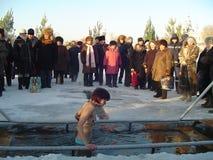 Het meisje baadt in een ijs-gat op de rivier Royalty-vrije Stock Foto's