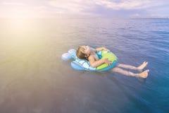 Het meisje baadt in het overzees met een cirkel Stock Foto