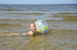 Het meisje baadt met een bal in water, Royalty-vrije Stock Foto