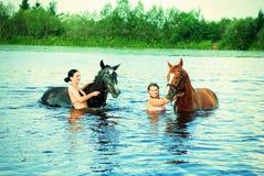 Het meisje baadt paard in een rivier stock afbeeldingen