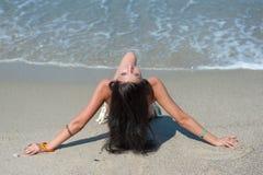 Het meisje in het badpak ligt op het strand Het gelukkige meisje bekijkt u terwijl zij op het strand was De zomer De vakantie van stock afbeeldingen