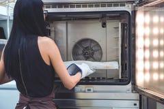 Het meisje Baker trekt zich van de oven vers gebakken bakkerijproducten terug van de oven royalty-vrije stock foto