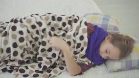 Het meisje in bed heeft een koude thuis, sterke hoest, keelpijn stock video